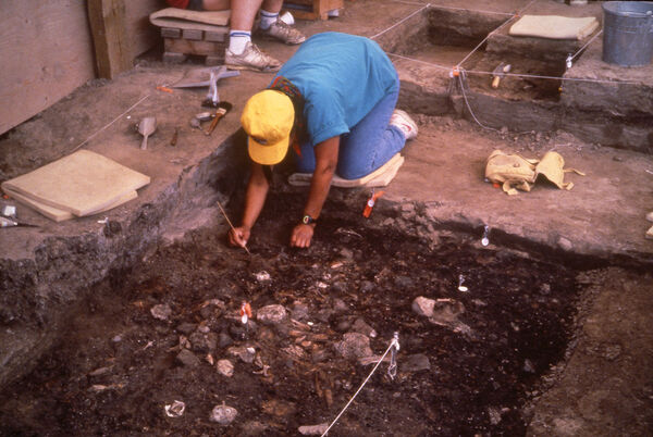 A member of the archeology team helps to uncover a 3,000-year-old hearth during a dig in August 1991 at The Forks. (The Forks North Portage Partnership)