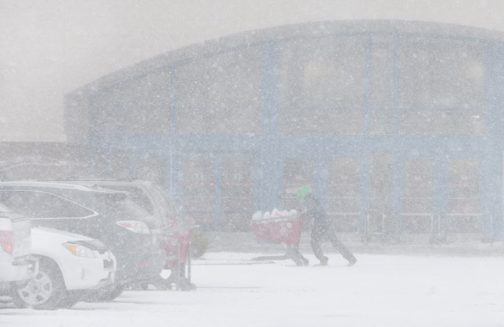 A shopper struggles in near-whiteout conditions as she leaves the Target store in Grand Forks, N.D., on Monday afternoon as a snowstorm named Gigi blows through.