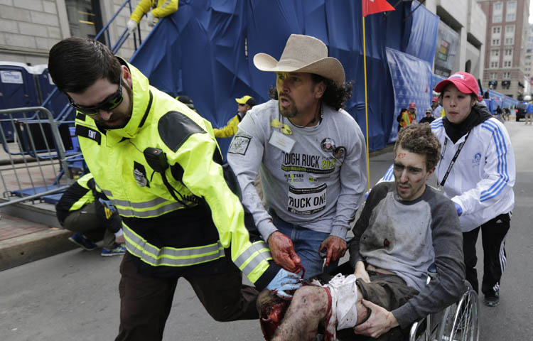 Medical responders run an injured man past the finish line the 2013 Boston Marathon following an explosion in Boston, Monday, April 15, 2013. Two explosions shattered the euphoria of the Boston Marathon finish line on Monday, sending authorities out on the course to carry off the injured while the stragglers were rerouted away from the smoking site of the blasts. (Charles Krupa / The Associated Press)