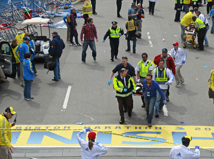 Medical workers wheel the injured across the finish line during the 2013 Boston Marathon following an explosion in Boston, Monday, April 15, 2013. Two explosions shattered the euphoria of the Boston Marathon finish line on Monday, sending authorities out on the course to carry off the injured while the stragglers were rerouted away from the smoking site of the blasts. (Charles Krupa / The Associated Press)