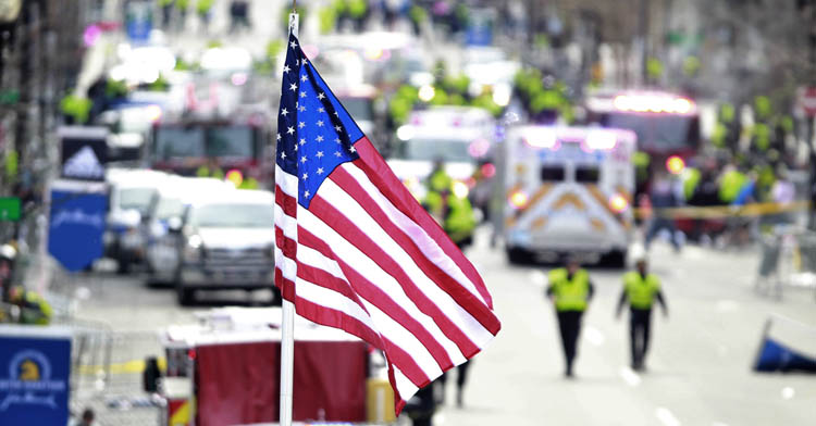 A flag flies over the finish line as medical workers aid injured people following an explosion at the finish line of the 2013 Boston Marathon in Boston, Monday, April 15, 2013. Two explosions shattered the euphoria at the finish line, sending authorities out on the course to carry off the injured while the stragglers were rerouted away from the smoking site of the blasts. (Charles Krupa / The Associated Press)