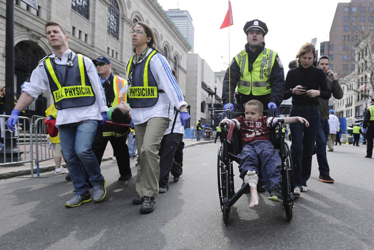 A Boston police officer wheels in injured boy down Boylston Street as medical workers carry an injured runner following an explosion during the 2013 Boston Marathon in Boston, Monday, April 15, 2013. Two explosions shattered the euphoria at the marathon's finish line on Monday, sending authorities out on the course to carry off the injured while the stragglers were rerouted away from the smoking site of the blasts. (Charles Krupa / The Associated Press)