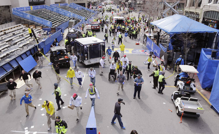 Police clear the area at the finish line of the 2013 Boston Marathon following an explosion in Boston, Monday, April 15, 2013.   Two explosions shattered the euphoria of the Boston Marathon finish line on Monday, sending authorities out on the course to carry off the injured while the stragglers were rerouted away from the smoking site of the blasts.