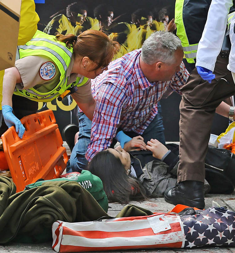 Medical workers aid injured people at the 2013 Boston Marathon following an explosion in Boston, Monday, April 15, 2013. Two explosions shattered the euphoria of the Boston Marathon finish line on Monday, sending authorities out on the course to carry off the injured while the stragglers were rerouted away from the smoking site of the blasts. (AP Photo/The Boston Globe, David L Ryan)   (David L. Ryan / The Associated Press)