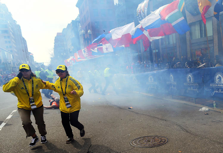 People react to an explosion at the 2013 Boston Marathon in Boston, Monday, April 15, 2013. Two explosions shattered the euphoria of the Boston Marathon finish line on Monday, sending authorities out on the course to carry off the injured while the stragglers were rerouted away from the smoking site of the blasts. (AP Photo/The Boston Globe,  John Tlumacki)   (John Tlumacki / The Associated Press)