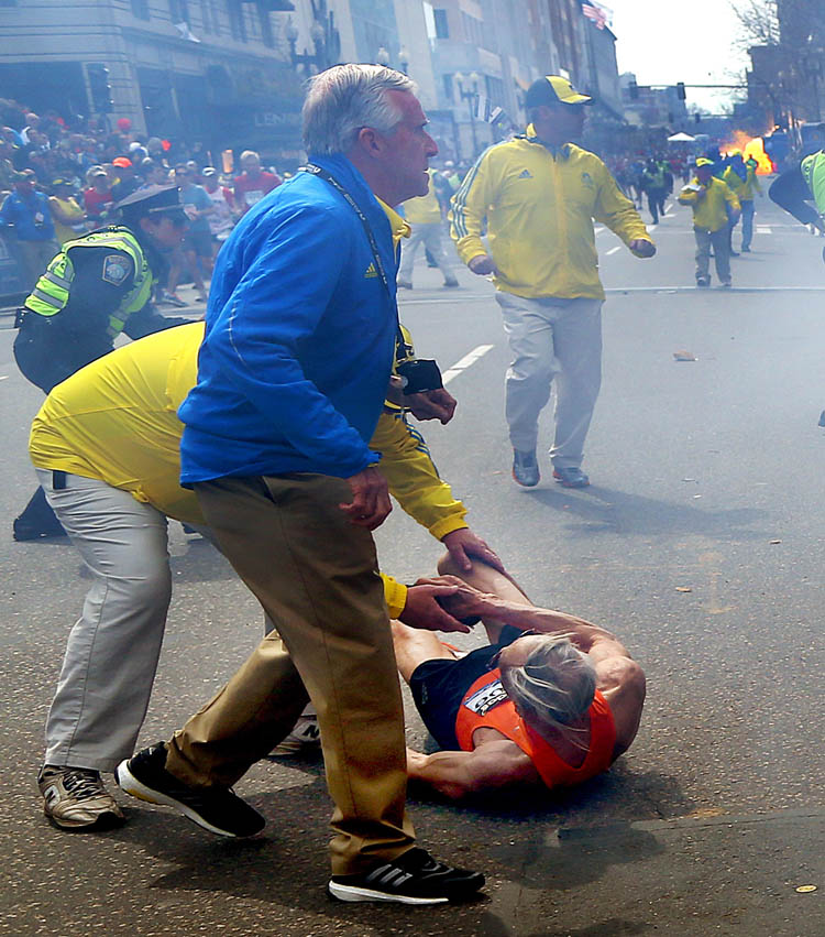People react to a second explosion at the 2013 Boston Marathon in Boston, Monday, April 15, 2013. Two explosions shattered the euphoria of the Boston Marathon finish line on Monday, sending authorities out on the course to carry off the injured while the stragglers were rerouted away from the smoking site of the blasts. (AP Photo/The Boston Globe,  John Tlumacki)   (John Tlumacki / The Associated Press)