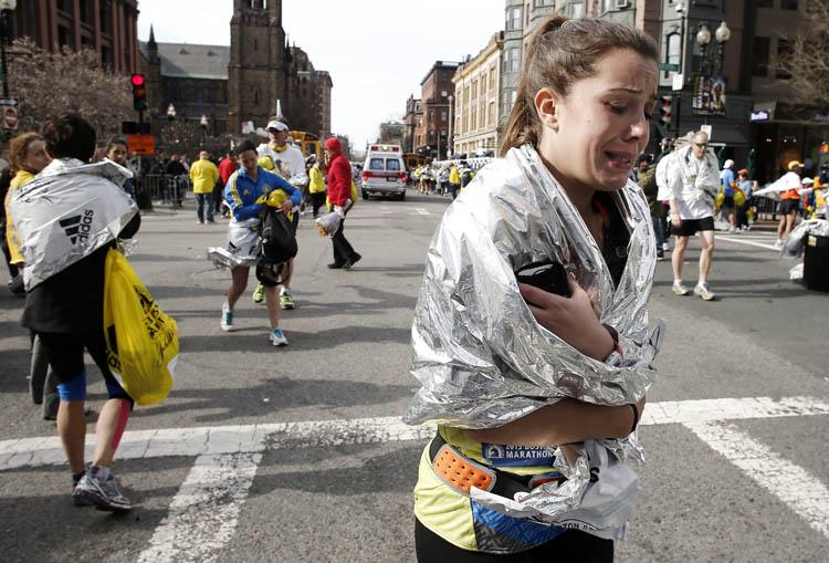 An unidentified Boston Marathon runner leaves the course crying near Copley Square following an explosion in Boston Monday, April 15, 2013. (Winslow Townson / The Associated Press)