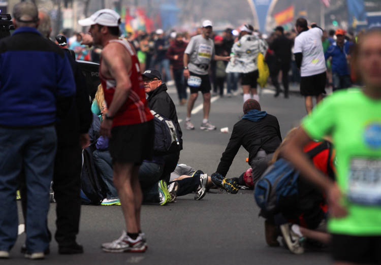 In this photo provided by The Daily Free Press and Kenshin Okubo, people react to an explosion at the 2013 Boston Marathon in Boston, Monday, April 15, 2013. Two explosions shattered the euphoria of the Boston Marathon finish line on Monday, sending authorities out on the course to carry off the injured while the stragglers were rerouted away from the smoking site of the blasts. (AP Photo/The Daily Free Press)