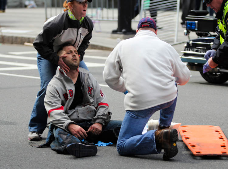 In this photo provided by The Daily Free Press and Kenshin Okubo, people assist an injured after an explosion at the 2013 Boston Marathon in Boston, Monday, April 15, 2013. Two explosions shattered the euphoria of the Boston Marathon finish line on Monday, sending authorities out on the course to carry off the injured while the stragglers were rerouted away from the smoking site of the blasts. (AP Photo/The Daily Free Press)