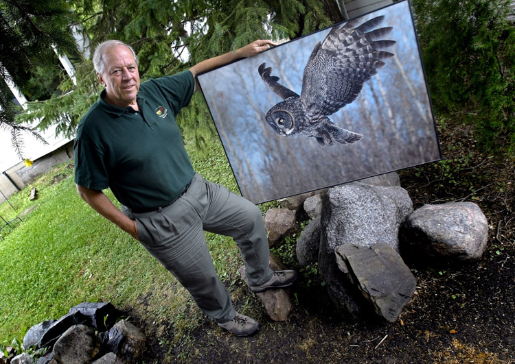 Wildlife artist Robert Taylor poses with a photo of a great grey owl.
