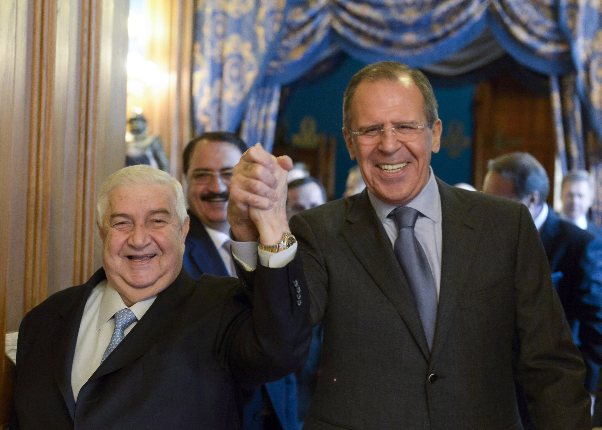 Russian Foreign Minister Sergey Lavrov, right, and Syrian Foreign Minister Walid al-Moallem enter a hall hand in hand for their talks in Moscow, Russia, Friday, Jan. 17.