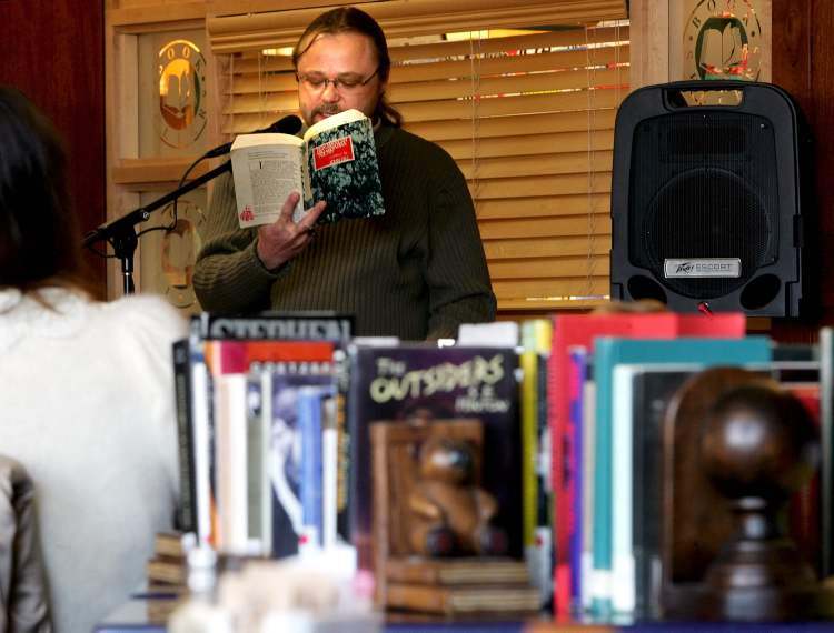 "February 25, 2006: Rene Huebener, a producer at radio station Power97 and aspiring poet, reads from the book New American and Canadian Poetry reading Milton Acorns' ""A series of poems,"" during the 24-hour Freedom to Read Marathon at McNally Robinson Booksellers, Grant Park. (MIKE DEAL / WINNIPEG FREE PRESS)"