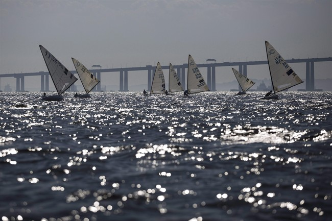 In this Aug. 3, 2014, file photo, athletes of the Finn class compete during the first test event for the Rio 2016 Olympic Games at the Guanabara Bay in Rio de Janeiro, Brazil. Amid reports of severe pollution and thousands of dead fish at the sailing venue for the 2016 Rio Olympics, Marcel Aubut says he is