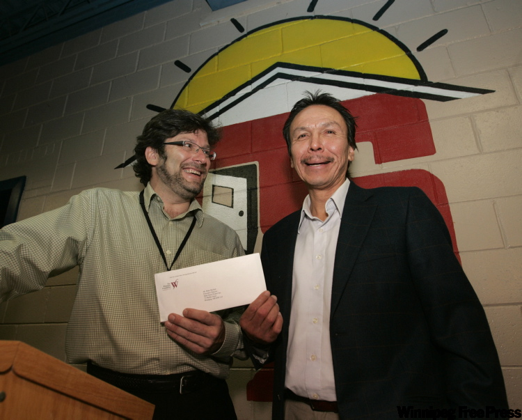 December 16, 2009: Faron Hall, right, gives a $1,000 cheque from the Faron Hall National Fund for The Homeless to Brian Bechtel, executive director of the Main Street Project. The Manitoba Life Saving Society also presented Hall with two medals for his efforts at a ceremony at the project. (WAYNE.GLOWACKI@FREEPRESS.MB.CA)
