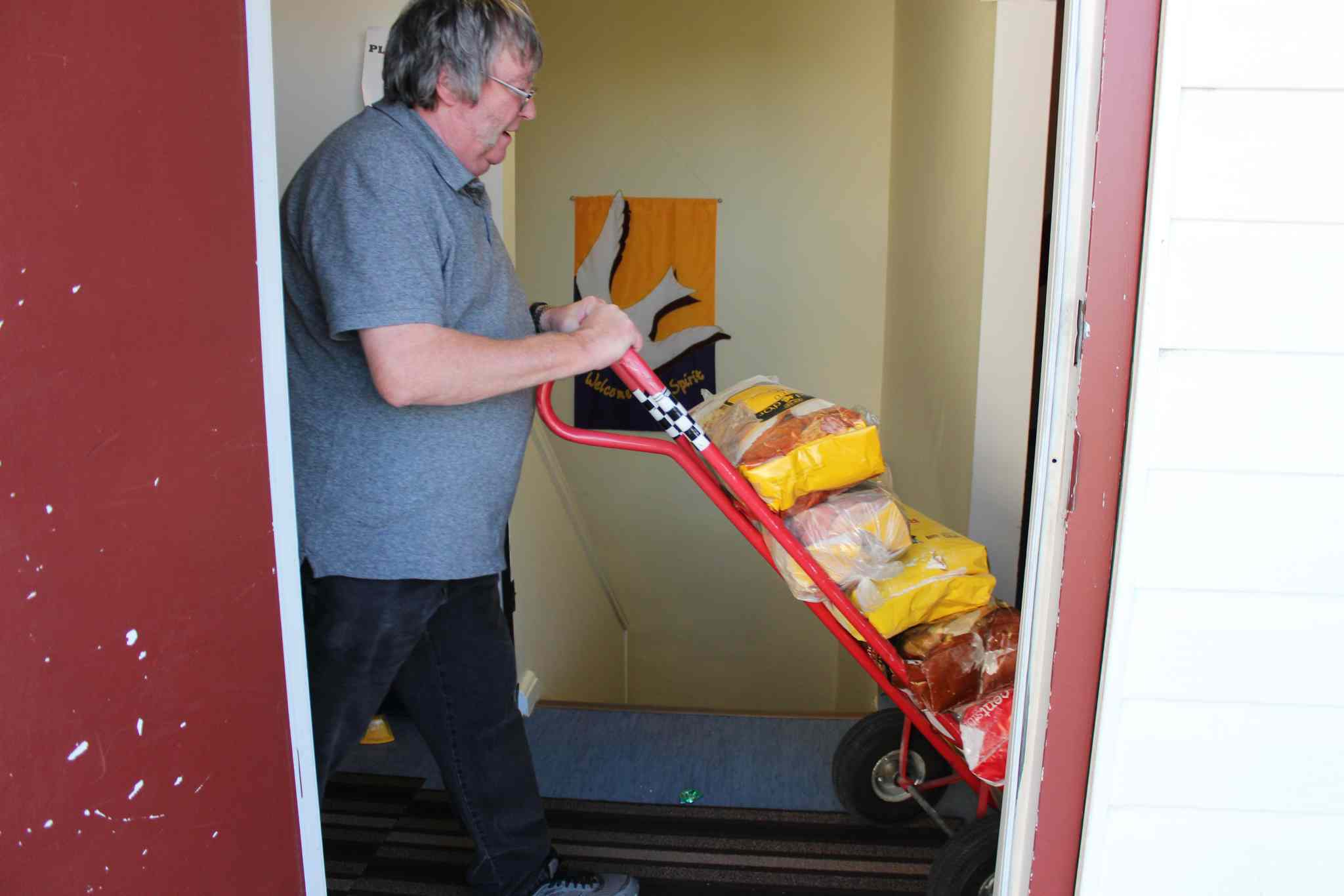Volunteer Norman Allen wheels a dolly full of flour into the Salvation Army food bank in Thompson.