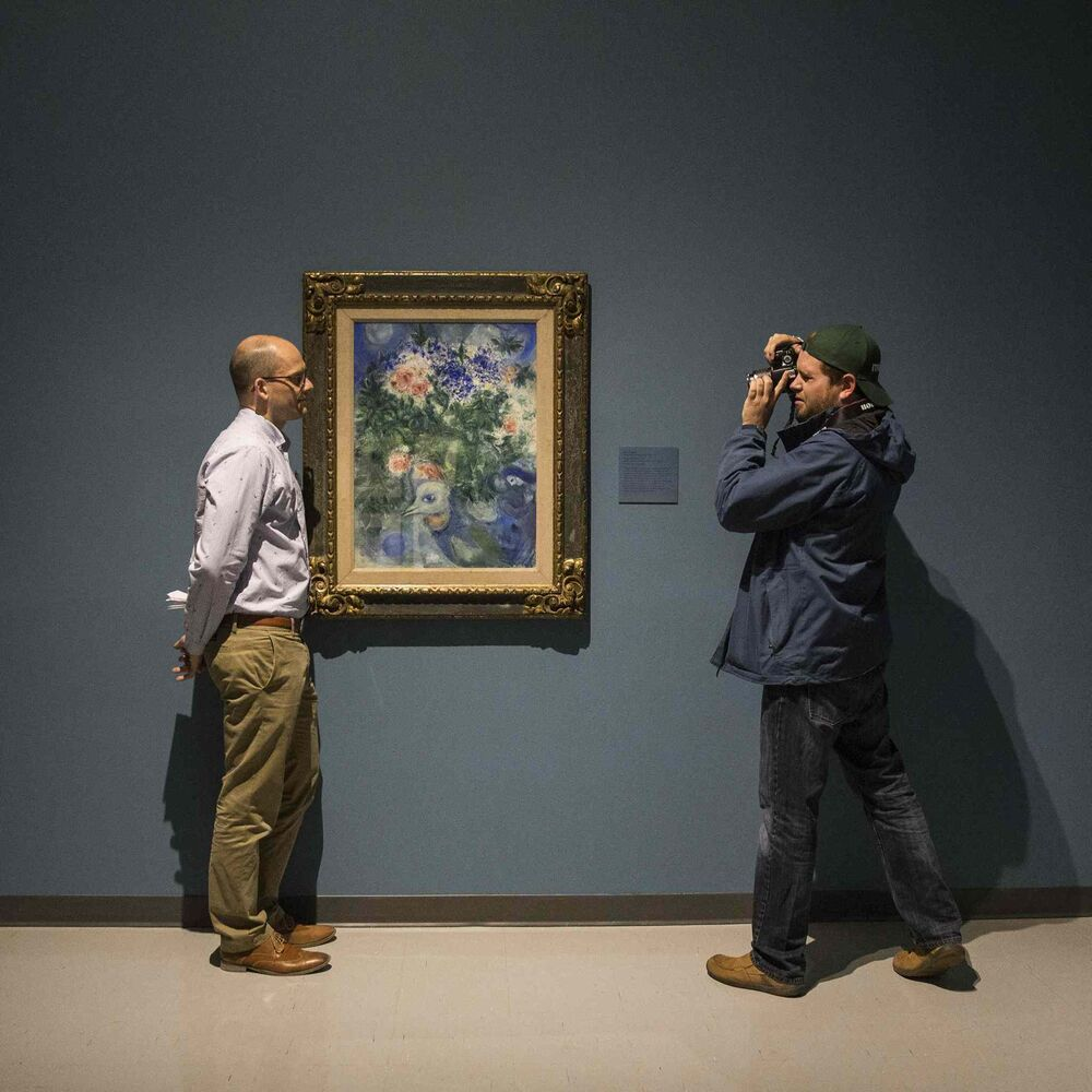 Andrew Kear, curator of Historical Canadian Art at the WAG, is photographed by a member of the media in front of Marc Chagall's Flower Still Life, 1935, watercolour, gouache on paperboard on canvas. May 26, 2016