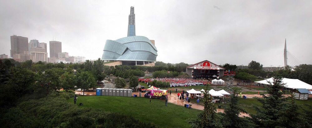 Nestled in the greenery of the Forks and with the city skyline as a backdrop,  a human flag is formed despite the weather at the Forks Tuesday. - Phil Hossack / Winnipeg Free Press