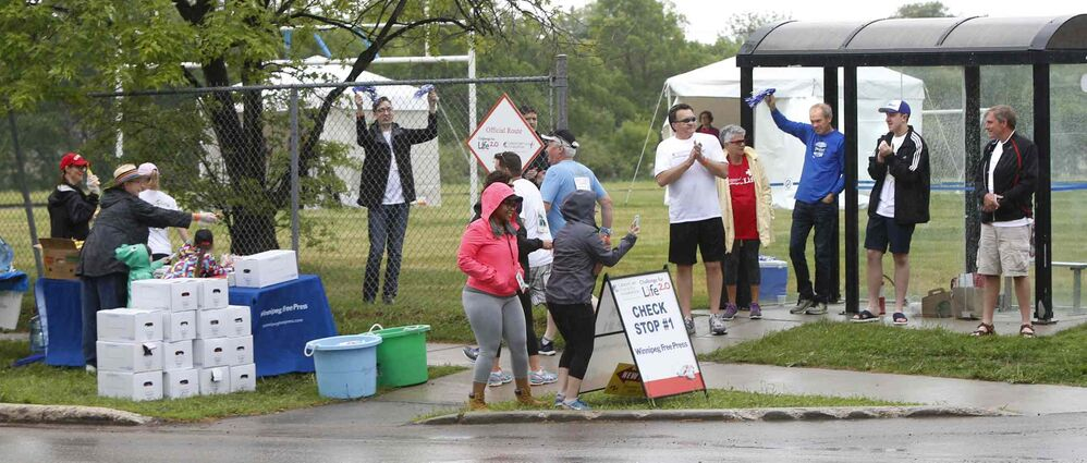 Walkers pass through a checkpoint referred to as the Check Stop along Grosvenor Avenue. The Check Stop was sponsored by the Winnipeg Free Press.<br>