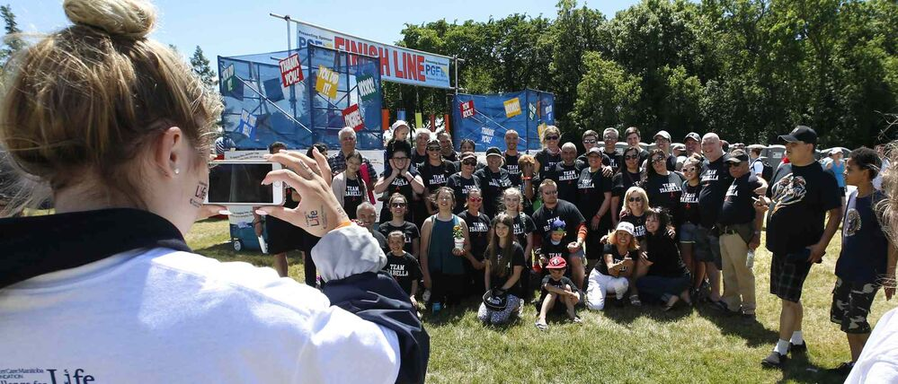 A volunteer snaps a group photo of Team Isabella at the finish line.<br>