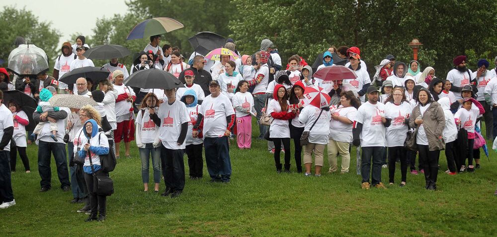 Participants wait under umbrellas for the flag formation to begin. - Phil Hossack / Winnipeg Free Press