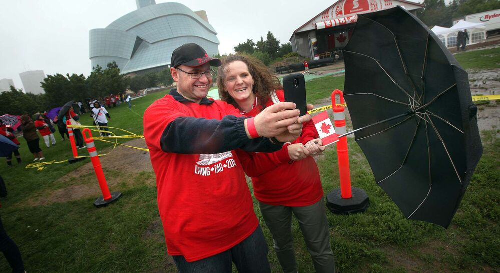 Ward Bruner and Jennifer Wilson hang onto their umbrella and smart phone trying to take a selfie in the blowing rain before taking part in the flag event. - Phil Hossack / Winnipeg Free Press