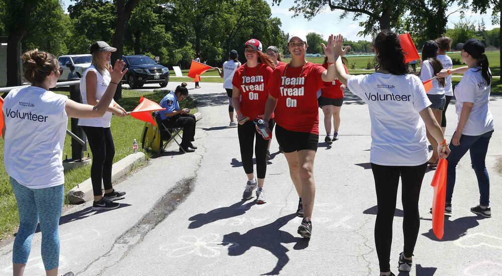 Volunteers cheer on members of Team Tread On as they near the finish line.<br>