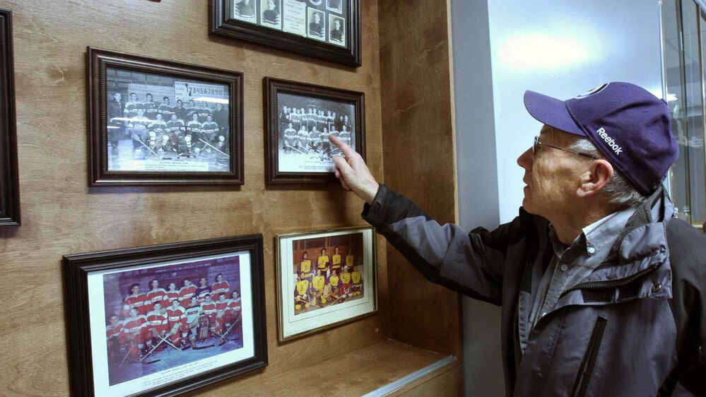 JOE BRYKSA / WINNIPEG FREE PRESS Walter Mueller looks at team pictures from back when he played inside the Manitou Community Arena.