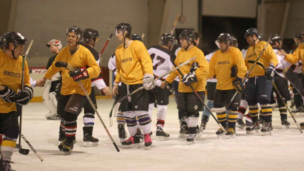 JOE BRYKSA / WINNIPEG FREE PRESS Team Kinosota (in yellow) and the Alonsa Aces shake hands after their game in a senior hockey tournament.