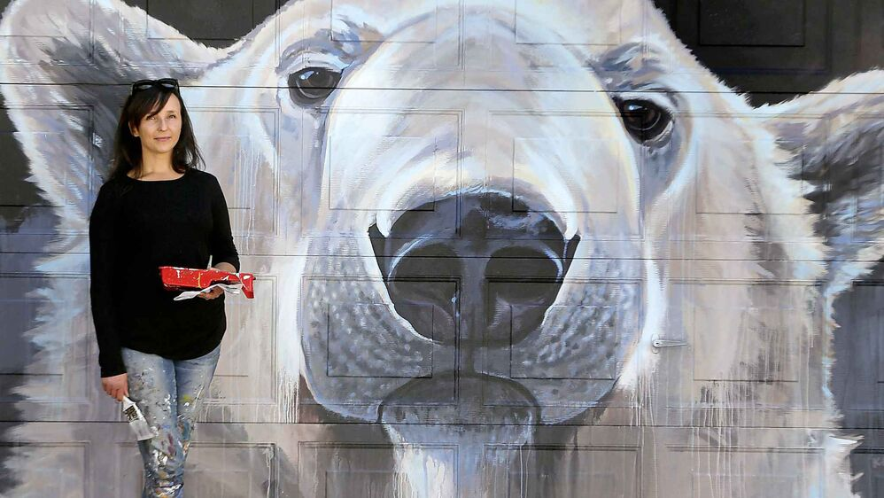 Winnipeg artist Kal Barteski with one of her arctic murals in the back lane between Ethelbert St. and Canora St. in Wolseley. - WAYNE GLOWACKI / WINNIPEG FREE PRESS