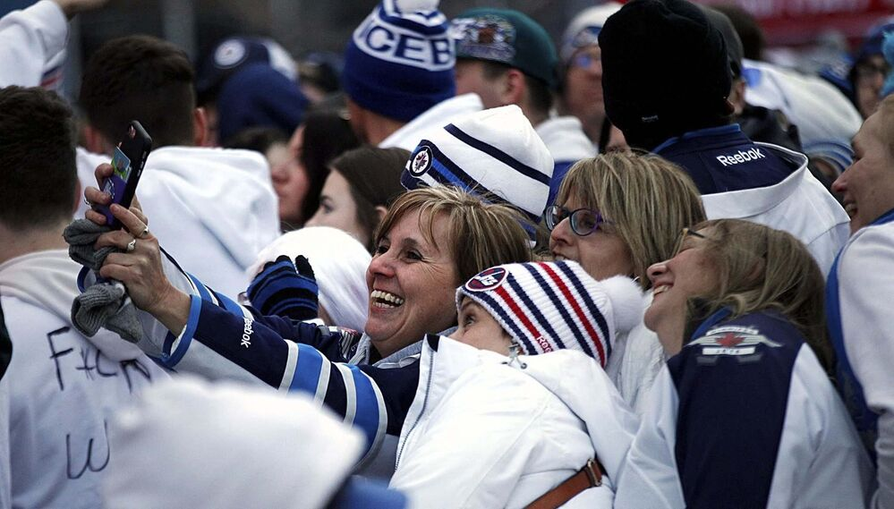 PHIL HOSSACK / WINNIPEG FREE PRESS -Jets revellers squeeze in a selfie in the standing room only crowd on Donald Street Friday. Stand-Up - April 13, 2018<br>