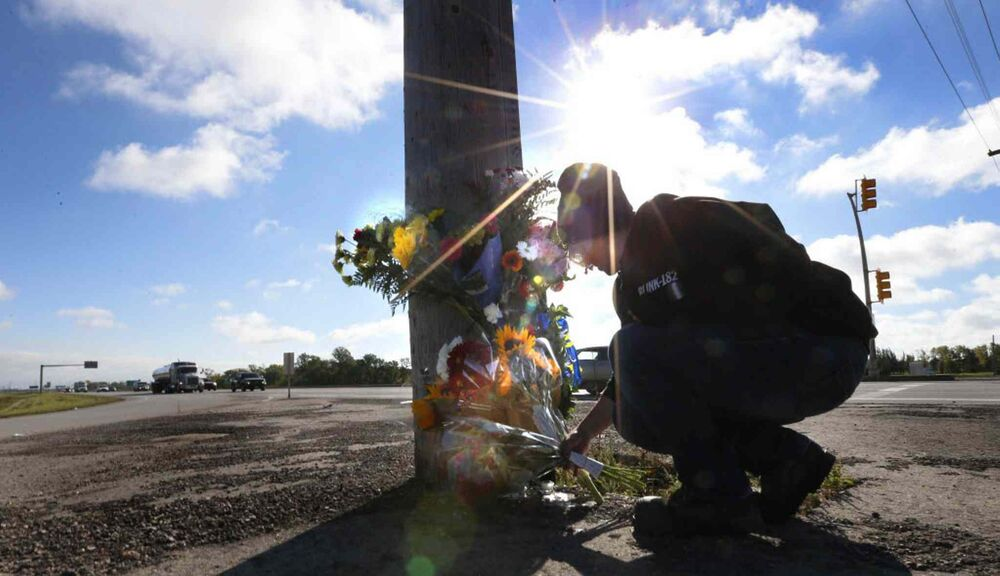 Lesley Eng places flowers at the roadside memorial at St. Anne's Road and the Perimeter Highway for her former biology teacher Michael Slobodian, who died after colliding with a dump truck while on his bicycle. September 8, 2016. -