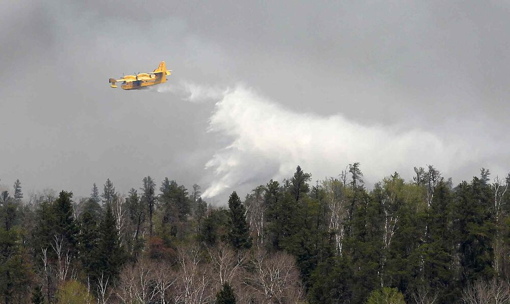 Water Bombers from Ontario dump water on the forest fire on the east end of Caddy Lake in the Whiteshell Monday. - JOE BRYKSA / WINNIPEG FREE PRESS