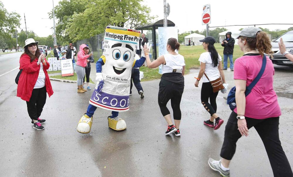 Winnipeg Free Press mascot, Scoop, gives high-fives to the participants as they pass through a checkpoint referred to as the Check Stop along Grosvenor Avenue. The Check Stop was sponsored by the Winnipeg Free Press.<br>