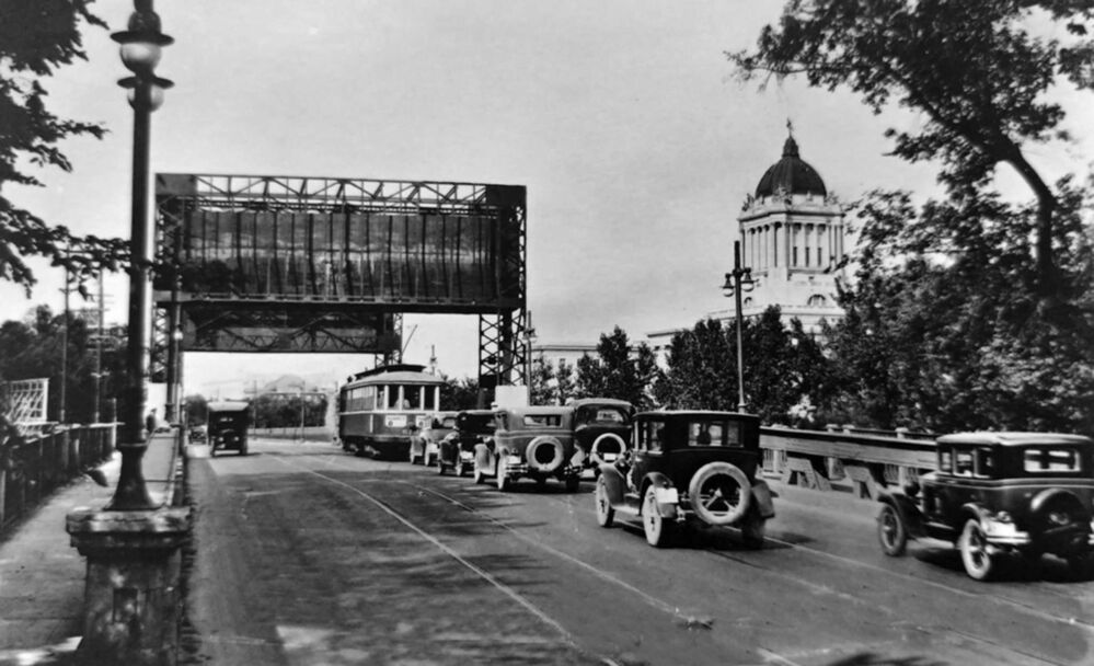 A gear from the old Osborne Street bridge, which stood from 1912 to 1976, can be seen in Gerald James Lynch Park near the new bridge.<br> - Archives of Manitoba