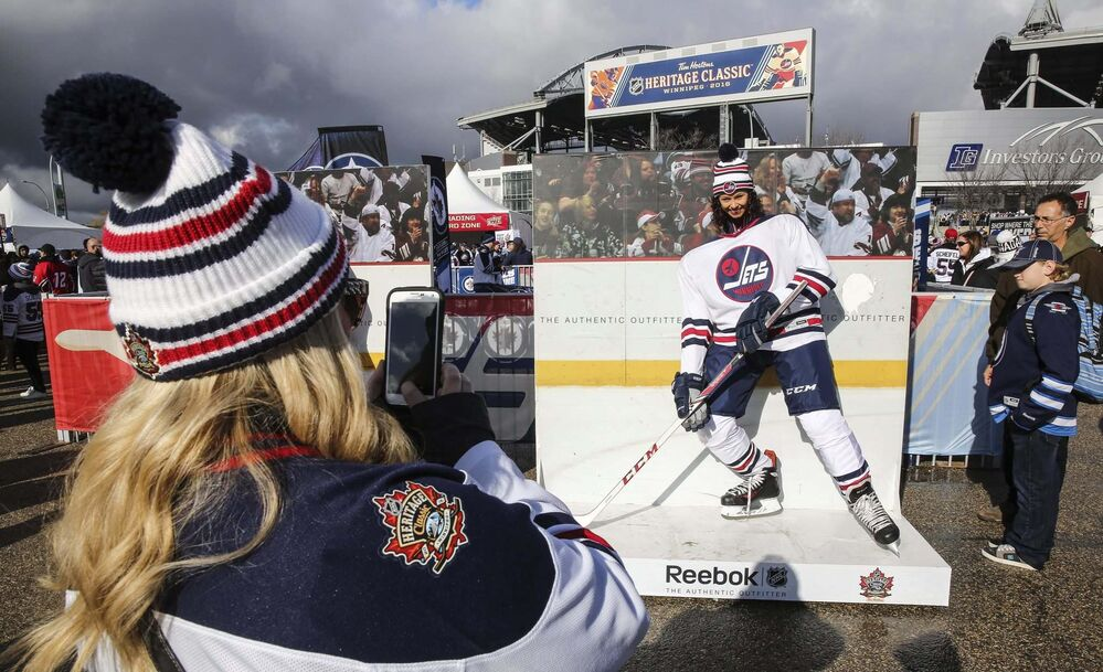 Karen Mitchell gets her photo taken by friend Susan Watson while taking in the party atmosphere at the Spectator Plaza across the street from Investors Group Field Sunday before the NHL game between the Winnipeg Jets and the Edmonton Oilers. - MIKE DEAL / WINNIPEG FREE PRESS