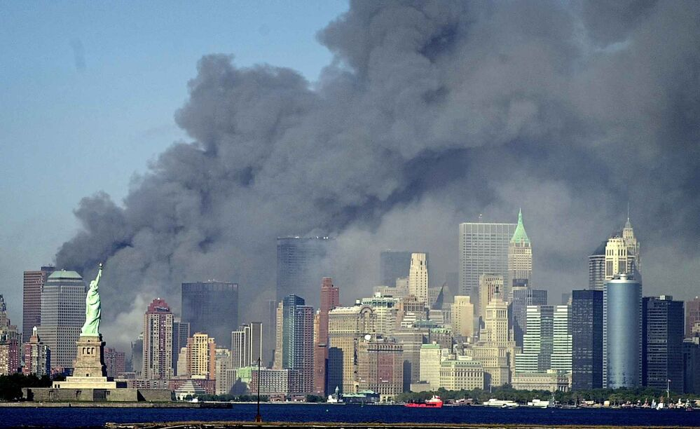 Thick smoke billows into the sky from the area behind the Statue of Liberty, lower left, where the World Trade Center was, on Tuesday, Sept. 11, 2001. (AP Photo/Daniel Hulshizer) -