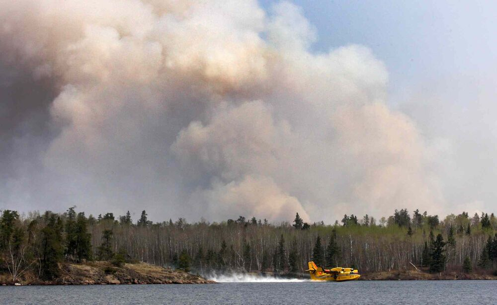 Water Bombers from Ontario scoop water in Caddy Lake to fight a forest fire near Nora Lake in the Whiteshell Monday. - JOE BRYKSA / WINNIPEG FREE PRESS