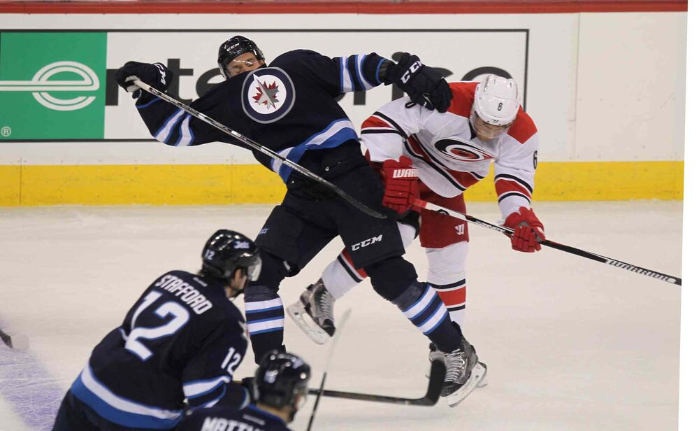 Winnipeg Jets Ben Chiarot (7) crashes with Carolina Hurricanes Klas Dahbeck (6) during first period of NHL action at the MTS Centre in Winnipeg on Thursday. - RUTH BONNEVILLE / WINNIPEG FREE PRESS