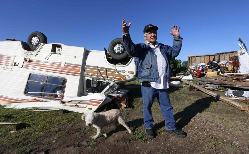 Clemance Assiniboine with his dog, Baby, in the back yard of his home on the Long Plain First Nation�where sheds at right, his house, and motor home were damaged after a tornado touched down the night before. July 21, 2016. -
