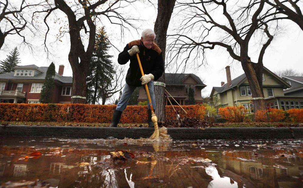 Robert Young in front of his home on Yale Avenue moves water and leaves towards a drain. October 28, 2016. -