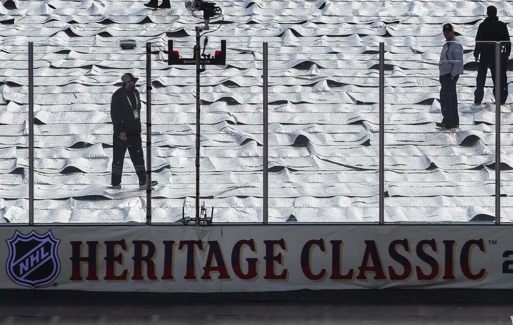 Rink maintenance staff keep an eye on the ice before the NHL game between the Winnipeg Jets and the Edmonton Oilers at Investors Group Field. Glare delayed the beginning of the game, rescheduled to begin at 3:53 p.m.<br> - MIKE DEAL / WINNIPEG FREE PRESS