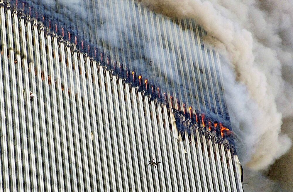 A person falls from the north tower of New York's World Trade Center as another clings to the outside, left, while smoke and fire billow from the building, Tuesday Sept. 11, 2001. (AP Photo/Richard Drew) -