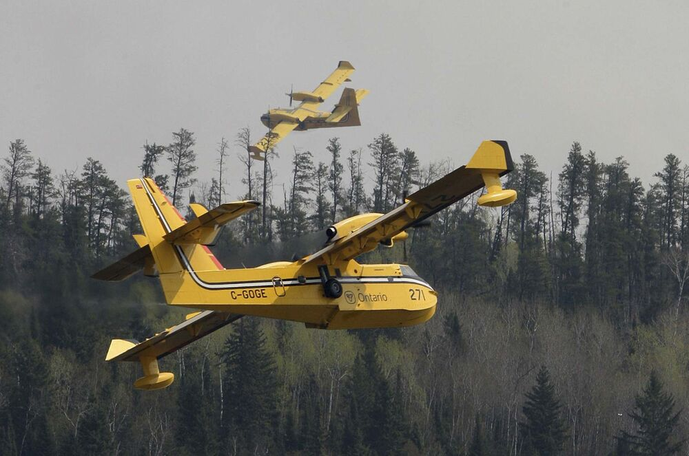 Water Bombers from Ontario scoop water in Caddy Lake to fight a forest fire near Noar Lake in the Whiteshell. - JOE BRYKSA / WINNIPEG FREE PRESS
