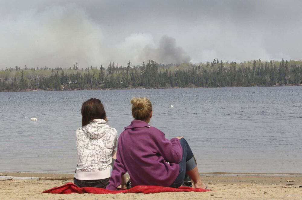 Cottagers Danica Brigham,left, and Onalee Ames watch as fire burns on the east end of Caddy Lake in the Whiteshell Monday. - JOE BRYKSA / WINNIPEG FREE PRESS