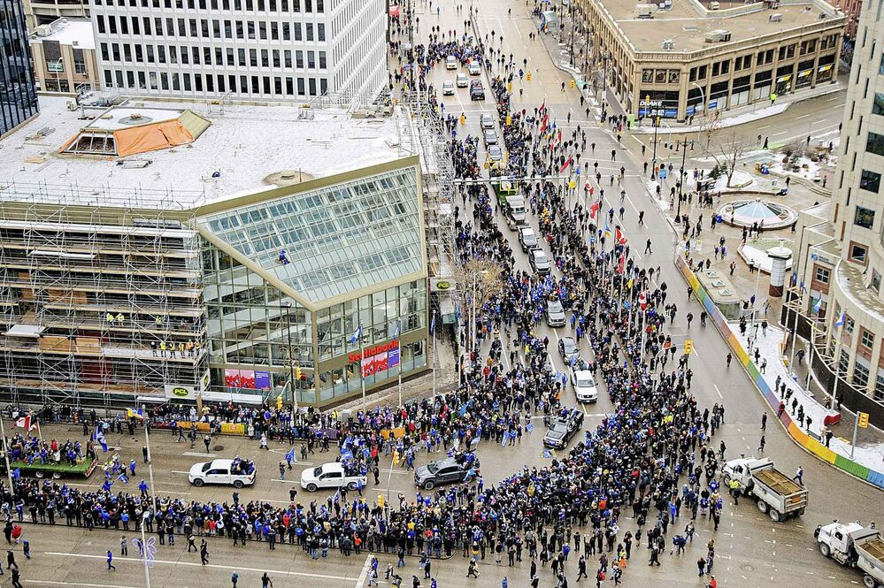Hundreds of Winnipeggers line up along Portage Ave and Main St Tuesday afternoon as they cheer on their Winnipeg Blue Bombers Grey Cup Champions as they parade through Portage Ave and Main St. (Mike Sudoma / Winnipeg Free Press)
