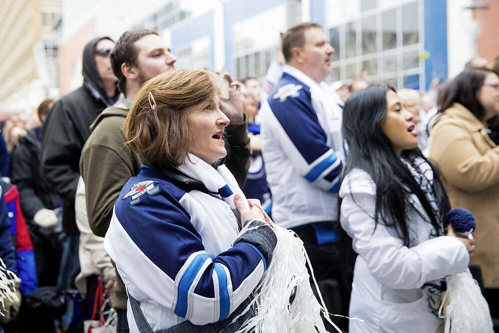 MIKAELA MACKENZIE / WINNIPEG FREE PRESS<br>Tammie Beauchemin sings the national anthem at the Jets whiteout party on Donald St.<br>