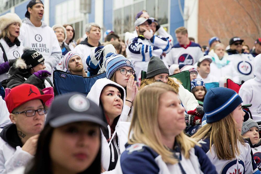 MIKAELA MACKENZIE / WINNIPEG FREE PRESS<br>Fans watch the first period at the Jets whiteout party on Donald St.<br>