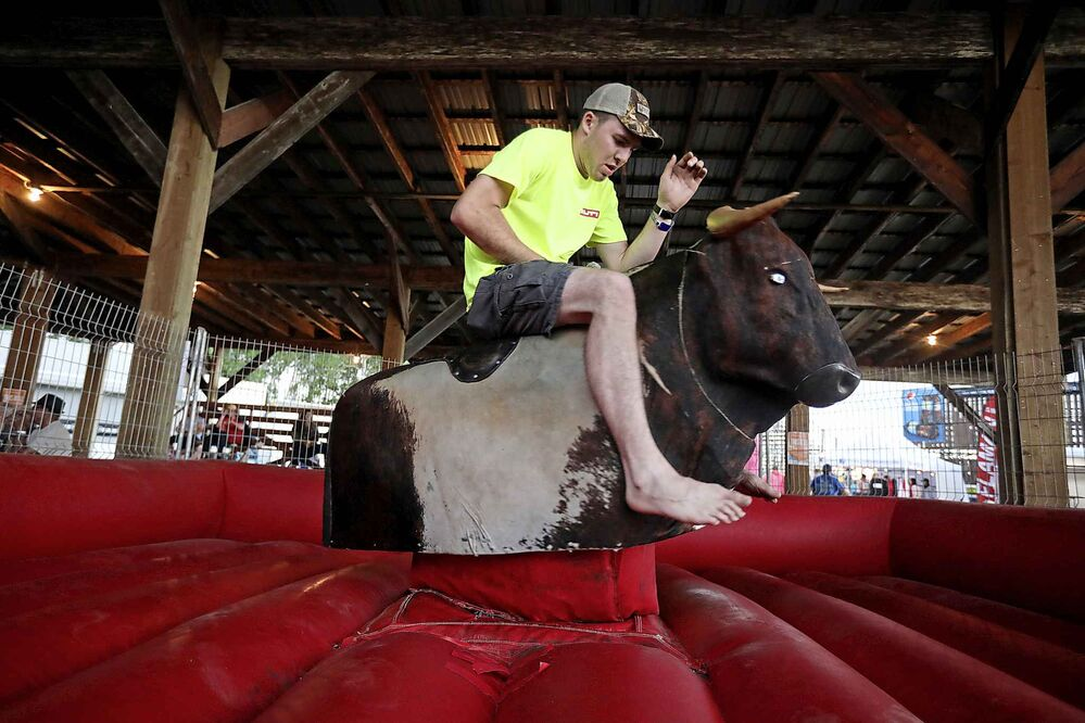 Chance Taylor tries to hang on while riding a mechanical bull. (Tim Smith / The Brandon Sun)