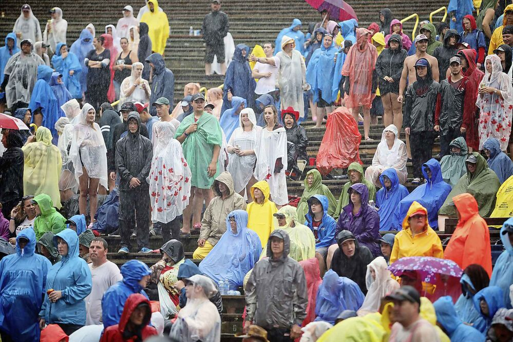 Country music fans wait out the rain at the mainstage during a sustained downpour at Countryfest Friday evening. (Tim Smith / The Brandon Sun)
