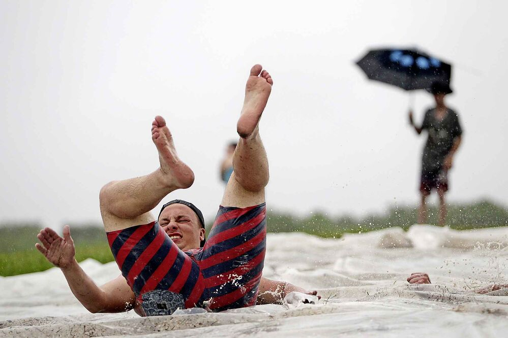 Festival-goers make the most of the rain on a slip-n-slide in the campground. (Tim Smith / The Brandon Sun)
